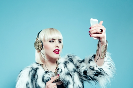 Portrait of posh blonde young woman wearing fur jacket, gold and headphone, taking a selfie using the smart phone. Studio shot, turquoise background.
